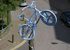 Sky blue BMX 'jumps' from the top of a telegraph pole