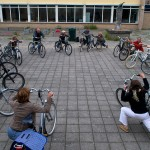 15 participants stretch alongside their bikes in a circle
