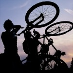 Two figures silhouetted against a purple sunset hold their bikes on back wheels