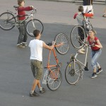 Participants mirroring each other's moves, bikes over shoulders and on back wheel