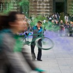 Woman spins bike with green and purple smoke effects
