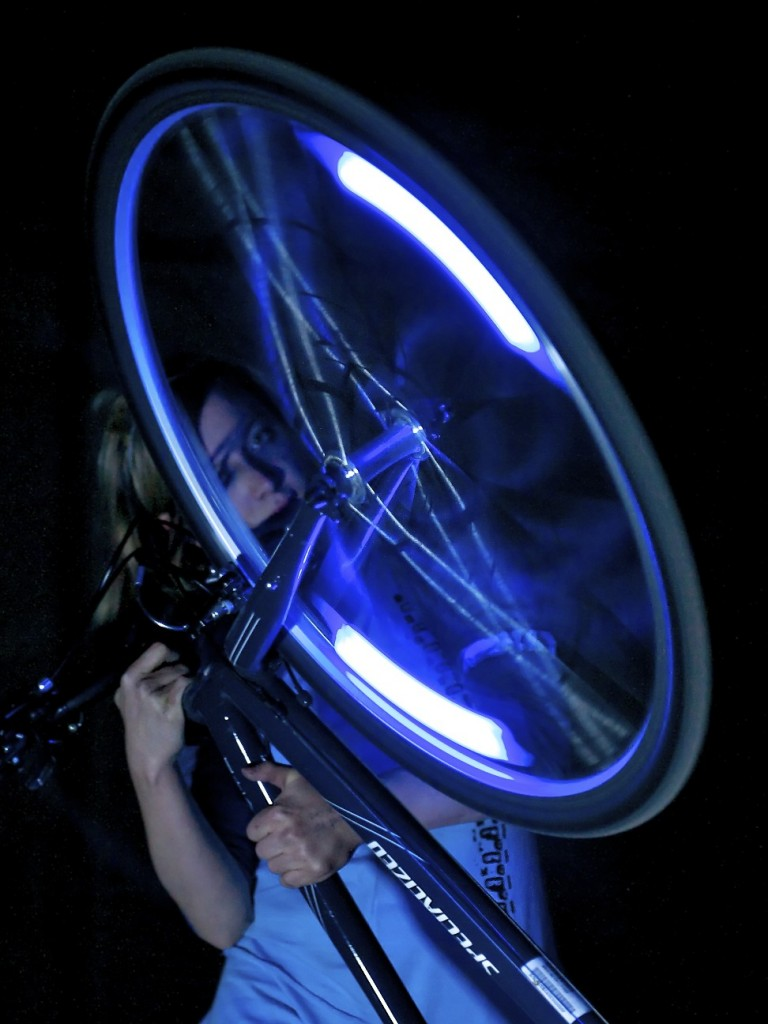 Female performer looking through blue lit, spinning wheel spokes