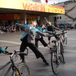 Diagonal line of costumed cyclists strike a pose
