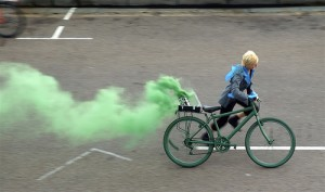 performer running with bike pouring green smoke from the back