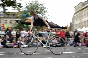 Imager of performer doing splits in the air alongside her bike