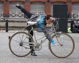 Mary leans across her bike and performs an arabesque, arm pointing towards the floor
