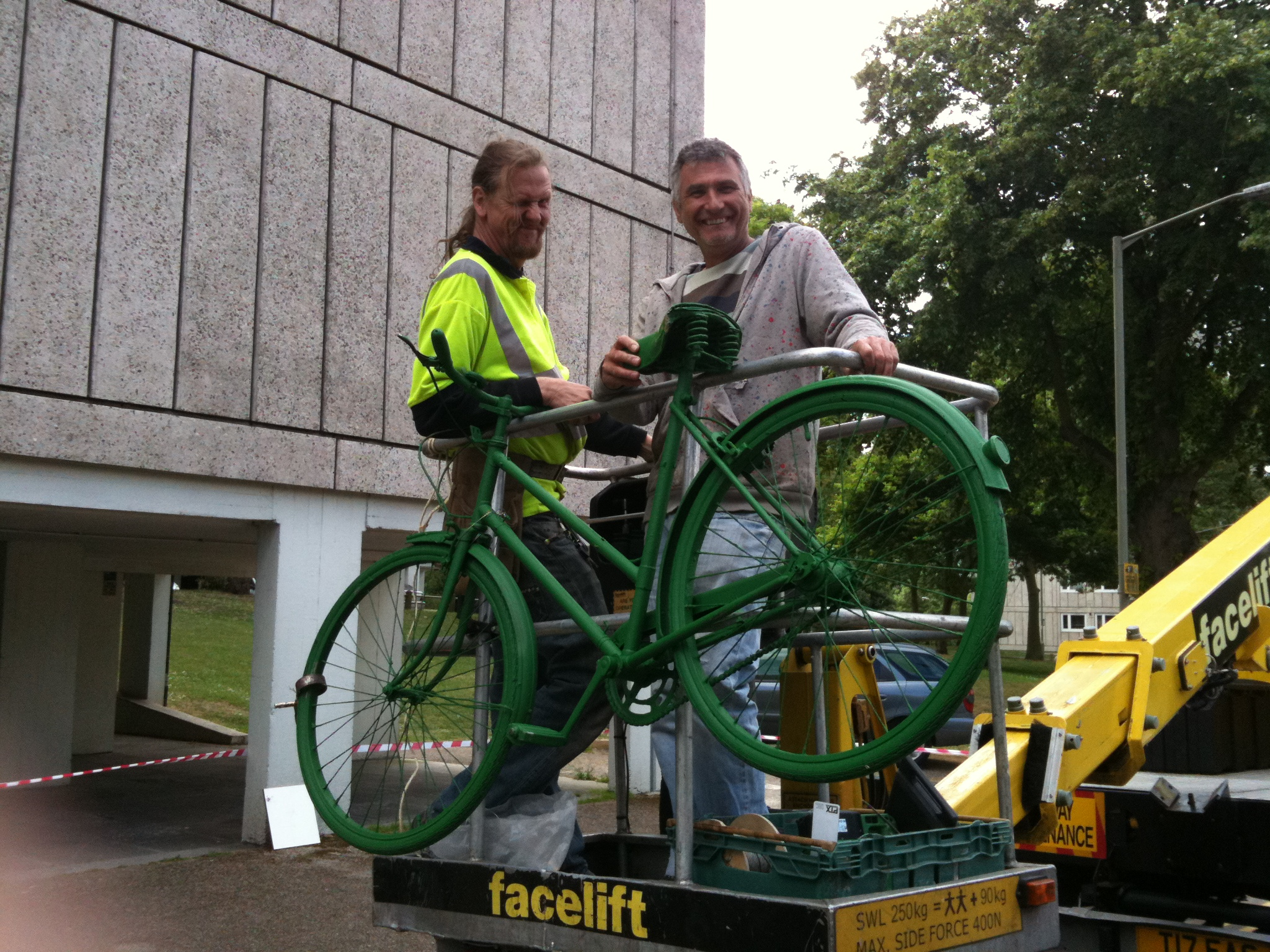 Performance Parking Technicians in cherry picker with a green bike