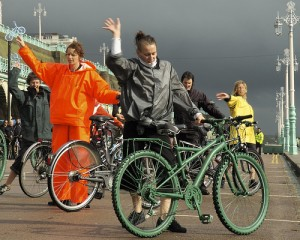 Janine Fletcher & dancers in wet weather gear, stand behind bikes & raise their arms, against a black sky