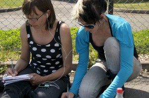 Image of Janine and Karen share ipod headphones, making notes on the show music
