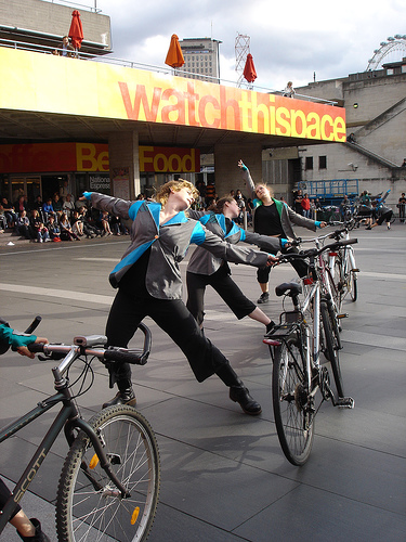 Performers dance with their bikes, arms outstretched