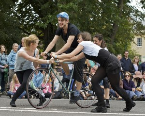 three performers hold onto a fourth's bike as he 'learns to ride'
