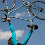 A dancer holds a bike above her head against a blue sky