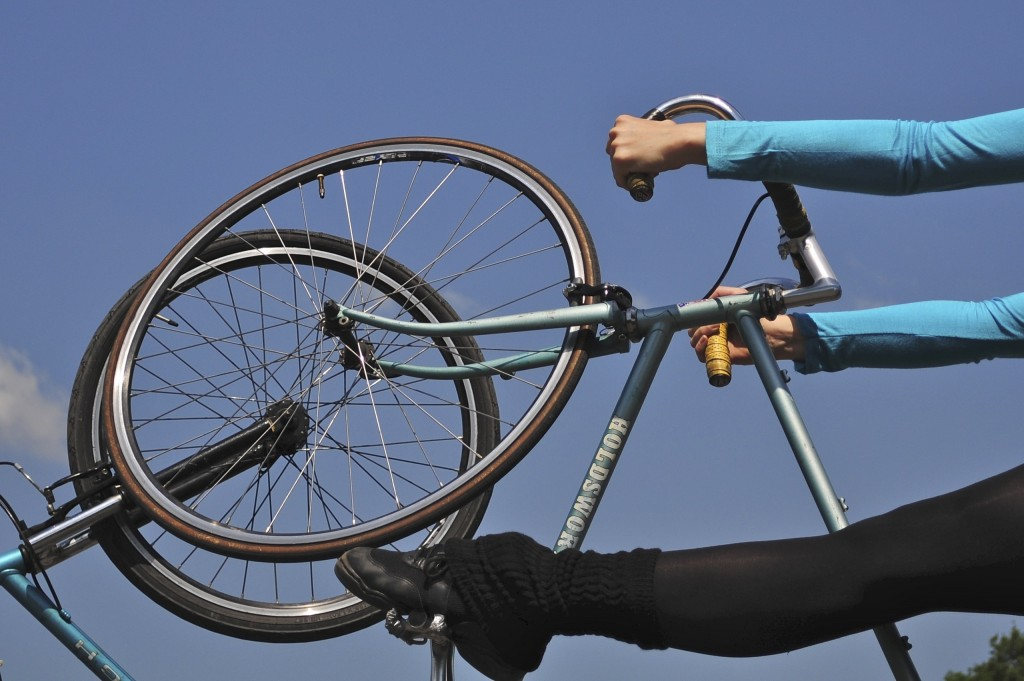 Two bike wheels meet, one held by a dancer's hands and foot