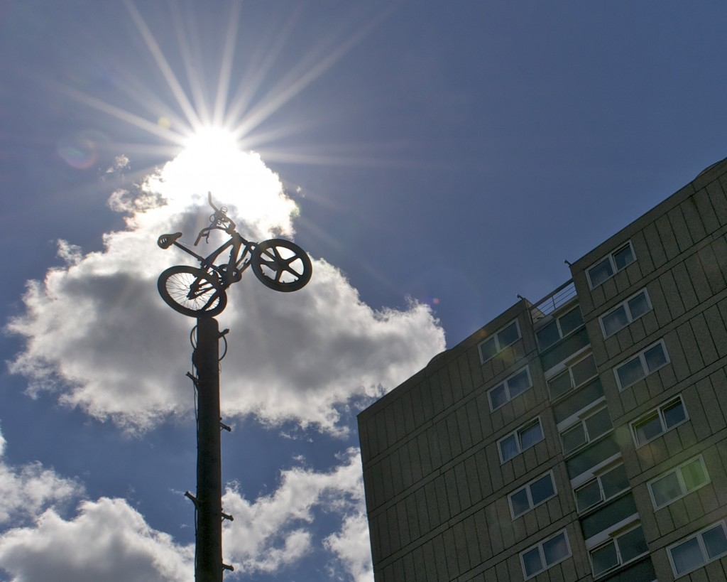 Silhouetted bike sitting atop a telegraph pole with sunburst