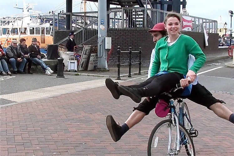 Female performer rides on the handle bars of her 'brother's' bike, smiling broadly