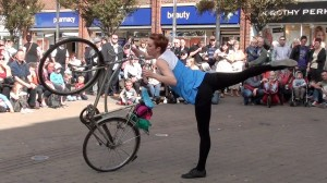 girl turns lifted bike on back wheel with one leg stretched out behind, in arabesque