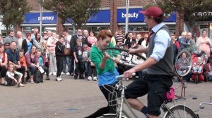 girl spins cycling boy around, both holding onto a bike wheel