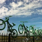 7 green painted bikes leap towards the sky from the top of a fence