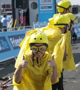 Four performers stand in a line in the Tour de France stage finish line, Bristol. Three performers look away and one smiles to the camera with two thumbs up. Performers wear bright yellow helmets, goggles and cycling capes