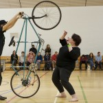 A performer holds his bike on its back wheel towering over another performer on the floor