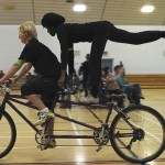 A partially sighted tandem rider stands on the cross bar with one leg raised in an arabesque, whilst the front rider continues to cycle