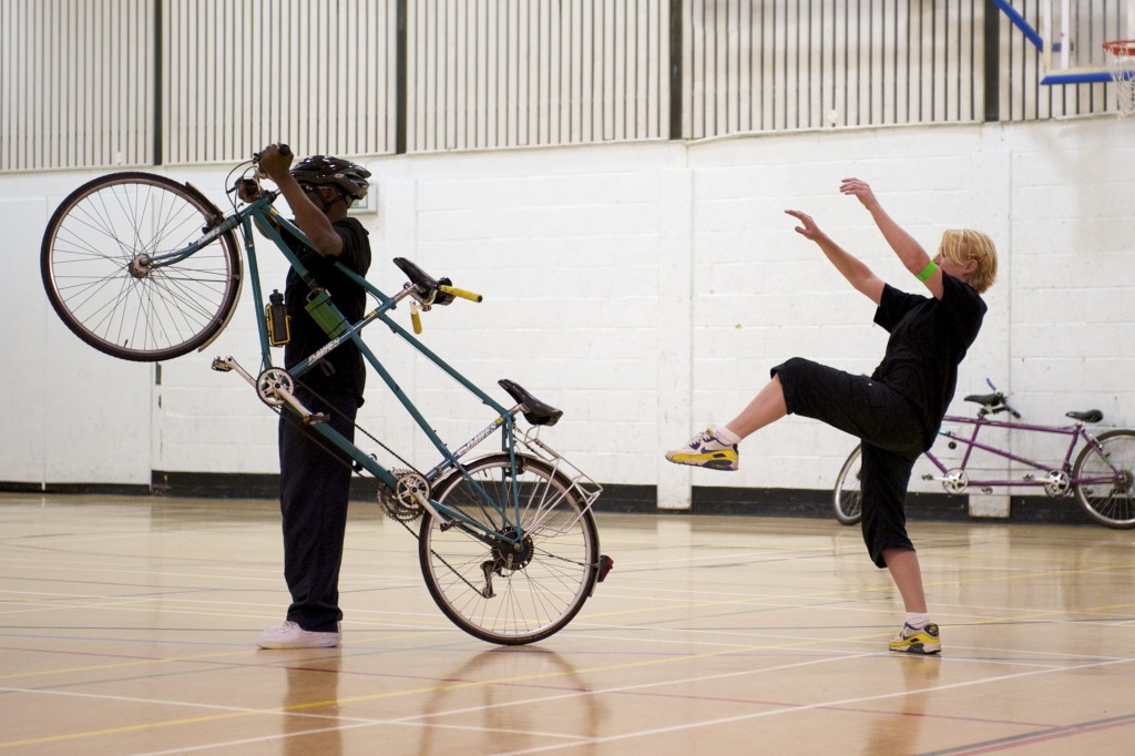 A blind man walks his tandem into the space.  He pulls the bike onto the back wheel and behind, a dancer mirrors, rearing up her leg & arms