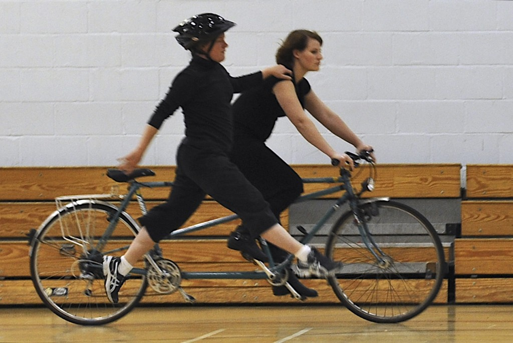 A partially sighted dancer on the ground, leaps alongside a moving tandem, with her hand on the rider's shoulder