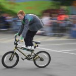 Young participant speeds past balancing on the cross bar of his bike