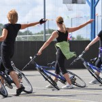 A line of three female performers hold bikes by the handlebars, leaning them close to the ground and standing with right legs through the frame, and right arms outstretched behind them