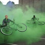Performers swing their bikes around amidst a cloud of green smoke