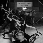Line of performers hold bikes by left hand leaning them to the floor, with right arms stretch behind them