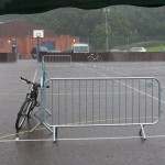 a solitary bike leans against a piece of crowd control barrier at the edge of the empty performance space, during a torrential rainstorm