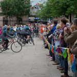 Audience behind bunting as performers on bikes turn into the distance