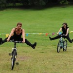 Two performers cycle with legs stretched out to the side