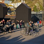 performers on bikes and on the ground, against the backdrop of fishermen's huts and East Hill