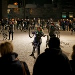 performers hold their bikes on the back wheels, during the night show