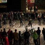 Performers in a line swing out from their bikes, with their arms pointing upwards diagonally.  In the foreground a silhouetted audience watch a solo performer perform a duet with her bike