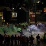 In the performance space, surrounded by audience, performers spin their bikes with green and violet smokes pouring from the back of the bikes