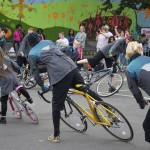 a group of performers lean their bikes to the left, with left feet on floor, and right legs raised
