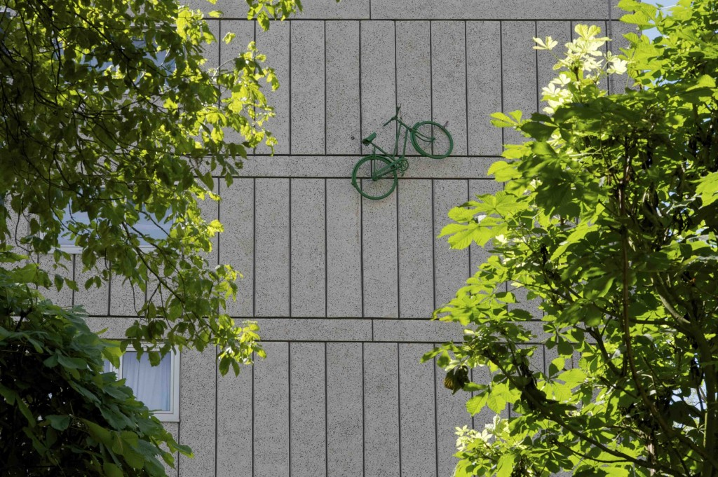 Green bicycle installed half way up the outside wall of a block of flats on the Alton Estate, Roehampton