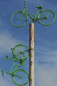 One green painted bicycle sits on top of a disused telegraph pole and another appears 'parked' on the side of the pole