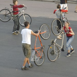participants work in pairs with their bikes, one pair lifting bikes onto back wheels, another pair hold bikes over their shoulders through the frames