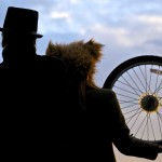 Two silhouetted figures lean into each other holding bike wheels. One wears a top hat, and the other a furry bear hat
