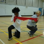 Two participants work together with a scarf, stretching it between them, crouching down and facing away from each other