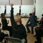 Seated warm up, participants stretch left arms into the air