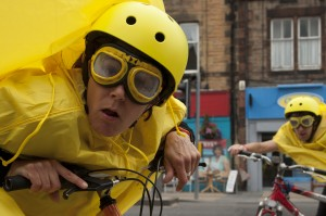 Performer, wearing a yellow helmet, goggles & rain mac, stares into the camera