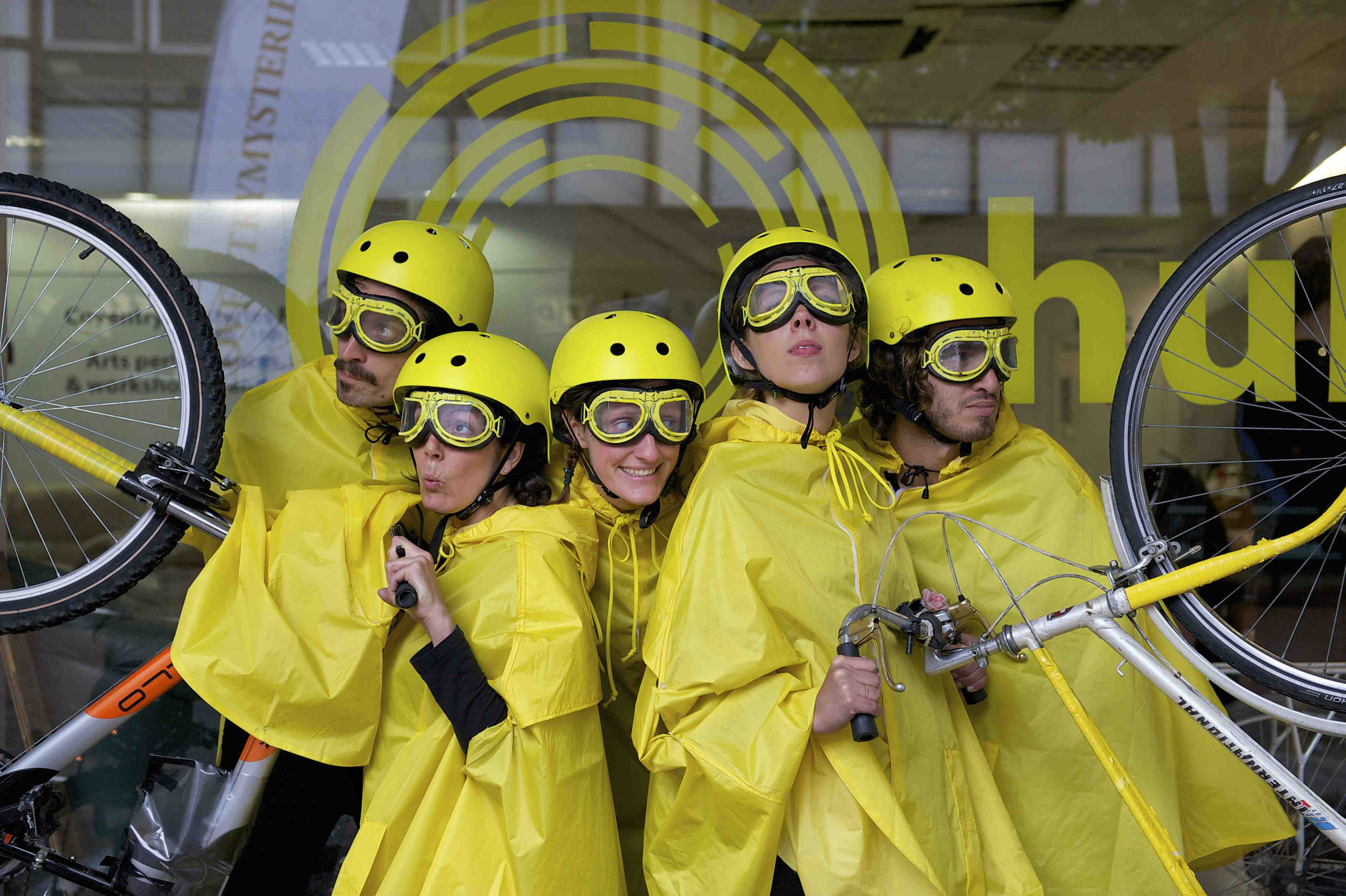 5 performers dressed in yellow cycling rain capes, yellow helmets and yellow goggles, strike a pose with 2 bikes
