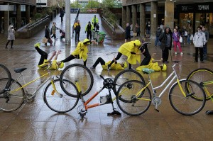 5 bicycles are lined up, some the right way up & others upside down. In the background, yellow dressed performers try to mimic the bike positions