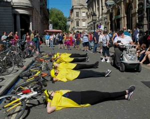 5 performers lie across the road with their heads resting on the saddles of their bikes, which are laid on the ground
