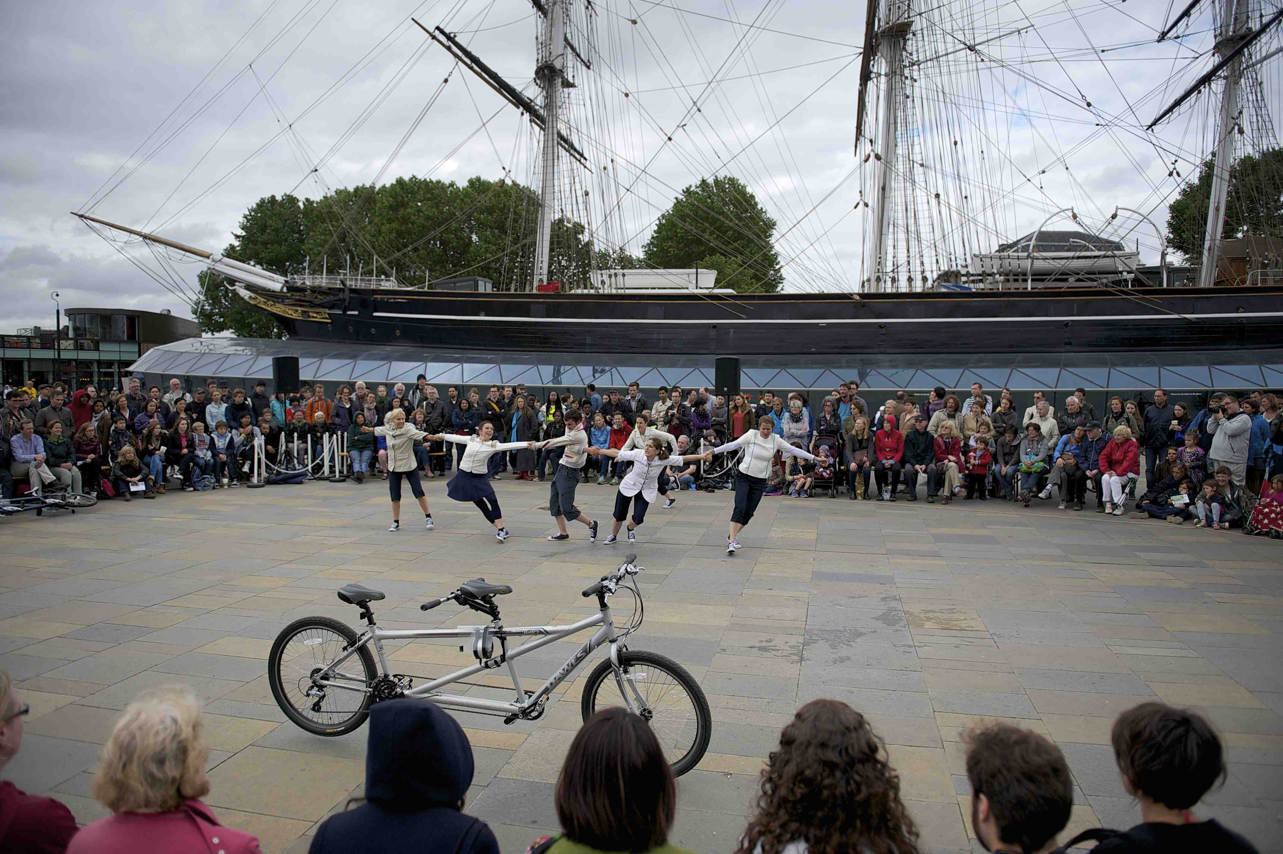 Performers in a line pulling Frustration, surrounded by a large crowd in front of the Cutty Sark